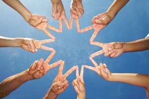 Viele Hände bilden einen Stern vor blauem Himmel